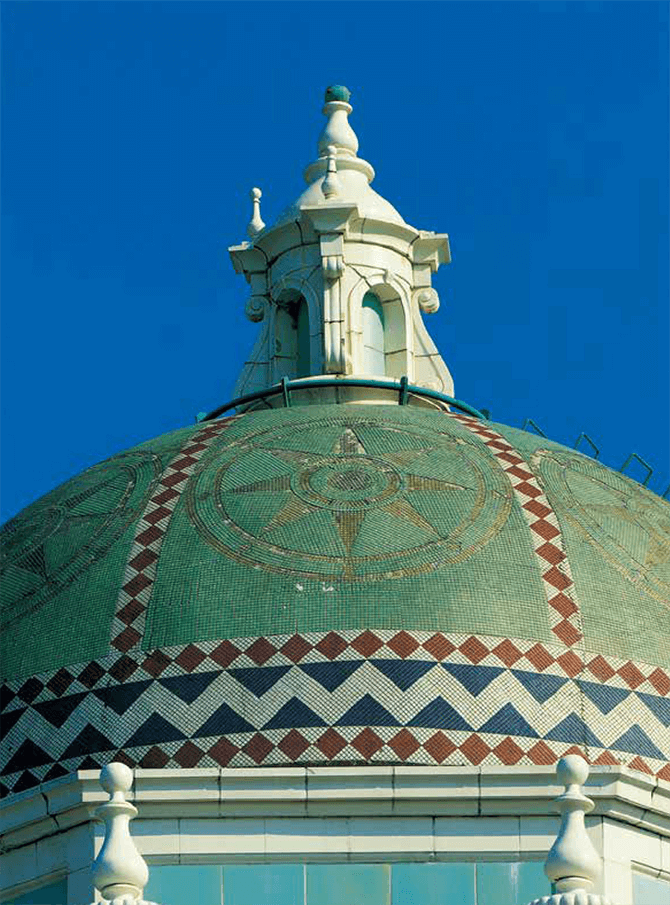 The Spanish-style Shizuoka City Hall building, built in1934, is topped with a terracotta tower and an Islamic-style dome roof. The roof is covered with green and gold mosaic tiles featuring a compass design. The terracotta and mosaic tiles were both produced by Ina Seito (INAX).